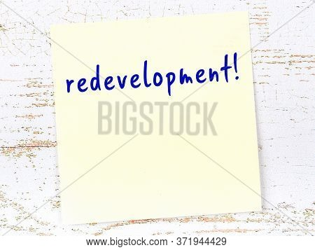 Concept Of Reminder About Redevelopment. Yellow Sticky Sheet Of Paper On Wooden Wall With Inscriptio