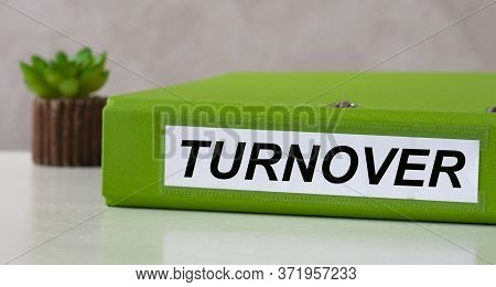 Turnover Word On Green Folder On A Light Background With Cactus. Business And Finance Concept.