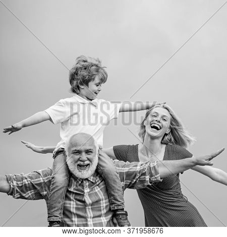Bearded Grandfather And Grandson Playing With On Sunny Day. Grandson Sits On The Shoulders Of His Gr
