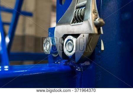 Adjustable Wrench Is Tightening The Chrome Screws On The Blue Metal Structure Or Disassembled Rack