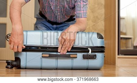Preparing Bag For Travel. A Man Trying To Pack Overfilled Suitcase