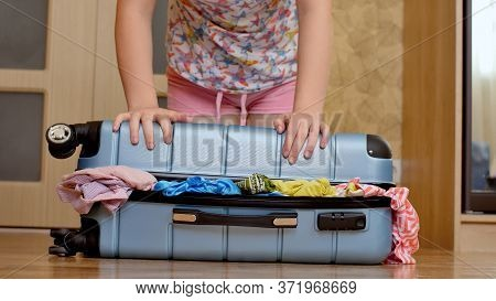 Preparing Bag For Travel. Young Woman Trying To Pack Overfilled Suitcase