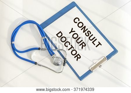 Consult Your Doctor Medical Reminder On Paper On Blue Clipboard With Stethoscope On White Table. Med