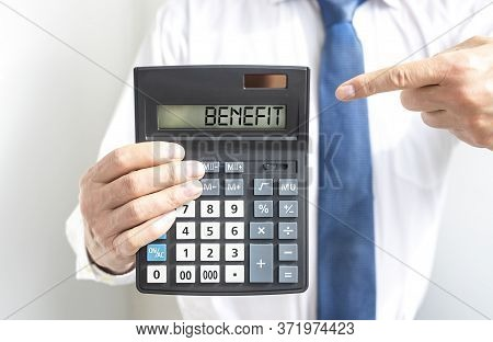 Word Benefit On Calculator In Hands Of A Businessman. Benefit Concept