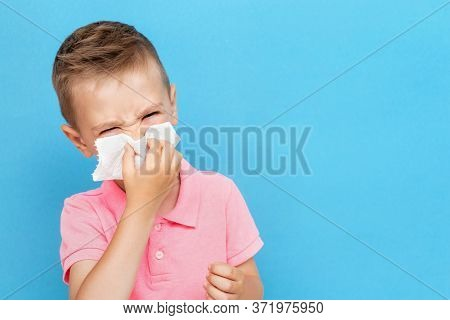 Sick Caucasian Kid Blowing Nose Into Tissue. Unhealthy Boy Suffering From Running Nose Or Sneezing