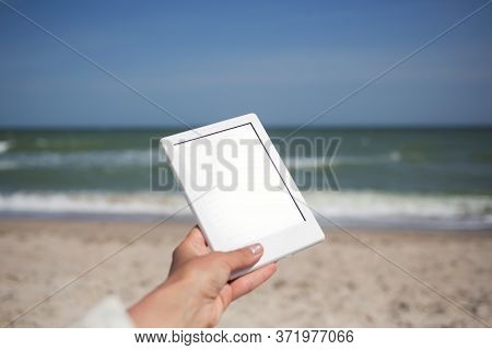 White Tablet E-book Reader With Shining Blank Screen At Sea Bech Background, Study, Learn, Read, Edu