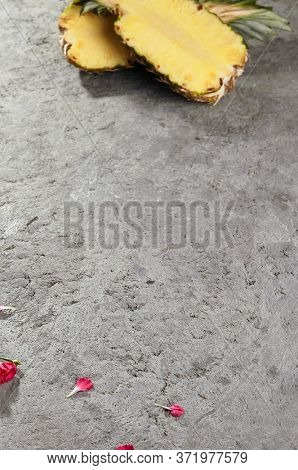 Pineapple cut in halves on rough grey cement surface. Tropical fruit on grungy concrete table. Delicate pink flower petals scattered on gray background. Trendy empty backdrop with text space