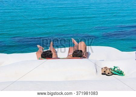 two tourists on a white rocky beach of Sicily with the sea by green-blue color water