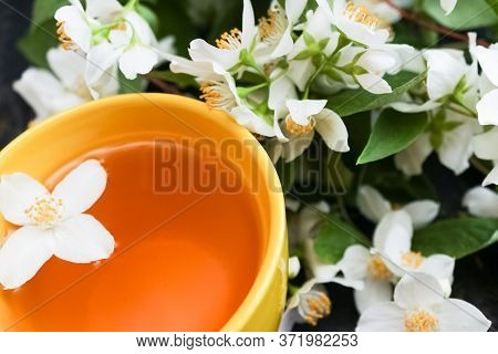 Cup Of Green Jasmin Tea, White Jasmine Flowers On Background. Copy Space. Teatime. High Quality Phot