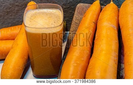 Carrot Juice And Tubercles (daucus Carota) On Light Concrete Background