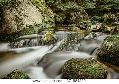 Waterfall photo. Long exposure photo of a beautiful Jedlova waterfall, Jizera mountains, Czechia. Motion blurr water in a mountain creek in deep forest. Hiking in a nature reserve.Fresh wild water
