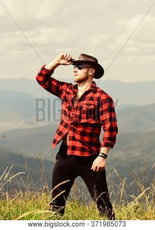 Looking Forward. Sexy Macho Man In Checkered Shirt. Cowboy In Hat Outdoor. Man On Mountain Landscape