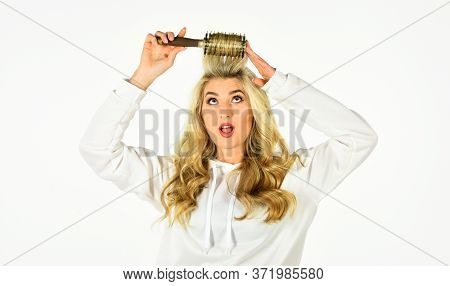 Look Your Best. Healthy Long Blond Hair. Beautiful Woman Curling Long Hair Using Curling Hairbrush.