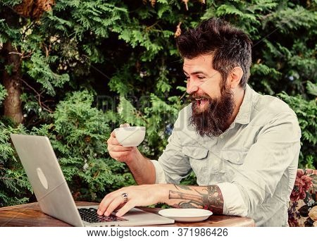 Computer Game Addiction. Happy Hipster Playing Computer Game In Summer Cafe. Bearded Man Player Enjo