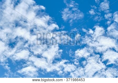 Blue Sky With Fluffy Clouds With Copy Space. Heaven In A Sunny Day. Wallpaper Concept.