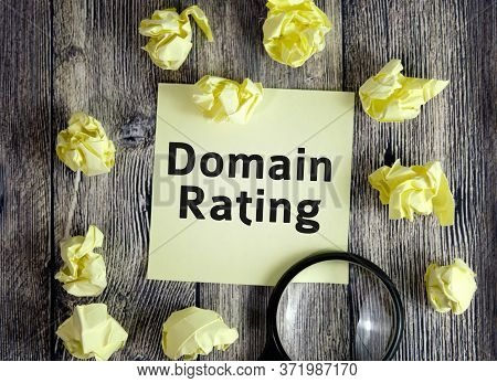 Domain Rating Seo Concept - Text On Yellow Note Sheets On A Dark Wooden Background With Crumpled She