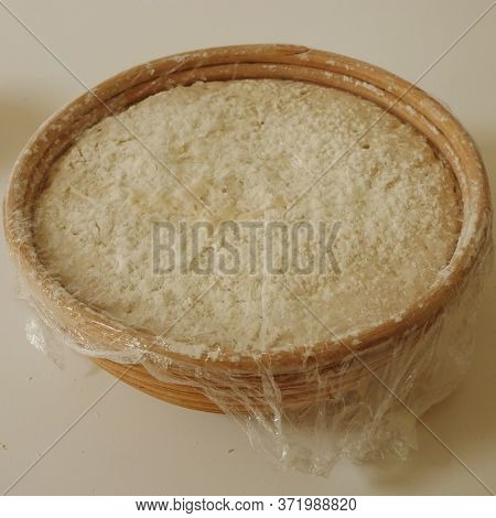 Sour Bread Dough Proving In Basket Covered With Cling Film