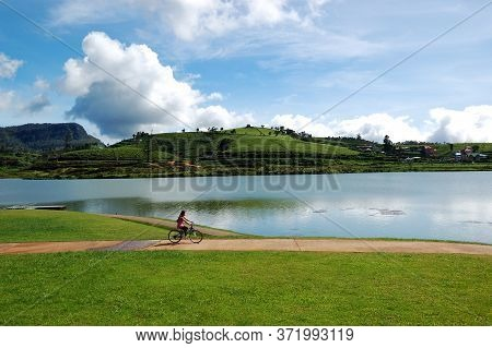 Nuwara Eliya, Sri Lanka - October 18 : The Girl Rides Her Bicycle Near Lake In Nuwara Eliya On Octob