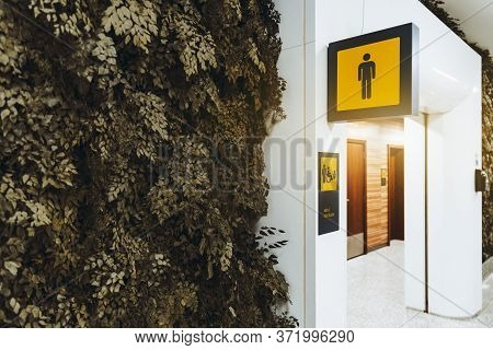 A Public Toilet Entrance For Men In A Modern Airport Terminal Building Or Railway Station Depot, Wit