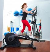 Aerobics cardio training woman on elliptic crosstrainer bicycle at gym poster