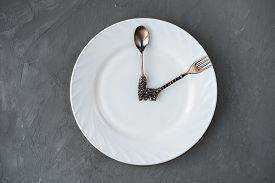 Lunch Time Concept. Spoon And A Fork On A Plate In A Shape Of Clock Hands. Time For Dinner Or Breakf