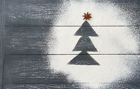 Flour On A Grey Wooden Table In A Shape Of Christmas Tree, Anise Seeds As A Star Over A Tree, New Ye