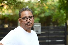 Indian Man Wearing Spectacles In A White T-shirt Outside A Gate Against A Gate And A Nature Backgrou