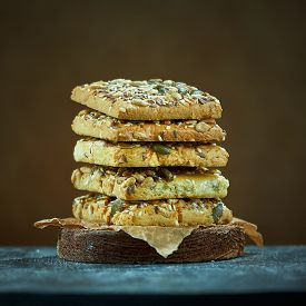 Square Cookies With Nuts And Seeds On Brown Background.