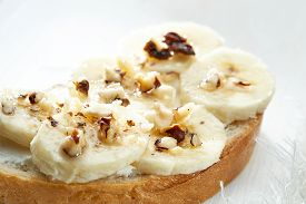 Sandwich With Banana Slices Sprinkled With Nuts Close Up On White Wooden Table.