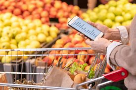 Hands of contemporary mature female customer with smartphone over food products in cart looking through shopping list