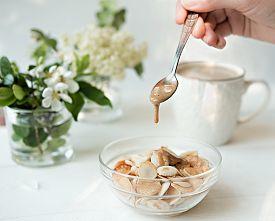 Mini Cereal Pancakes, Little Dutch Poffertjes. Woman Pouring Sauce On Pancakes. Little Pancakes In T