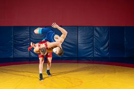 The Concept Of Fair Wrestling. Two Greco-roman  Wrestlers In Red And Blue Uniform Wrestling   On A Y