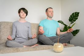 Father And Daughter Are Meditating, Sitting In Lotus Position On The Couch. Yoga At Home. Horizontal