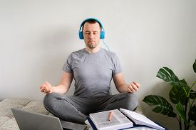 Work From Home. Young Man Sits On A Bed In Headphones And Listens To Music. Home Workplace. Break, R
