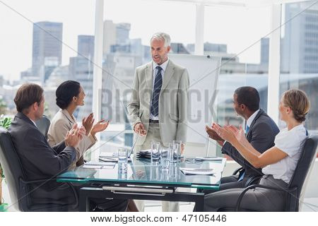 Colleagues applauding the boss during a meeting in the meeting room