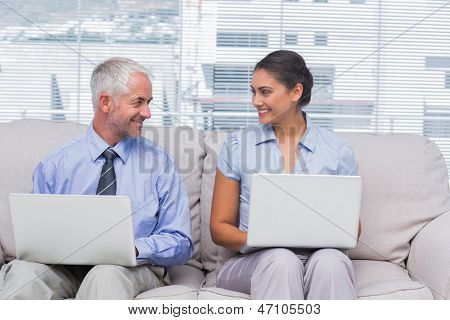 Business people using their laptops and smiling at each other on sofa in staffroom poster