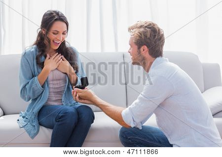 Handsome man doing a marriage proposal while offering his wife an engagement ring