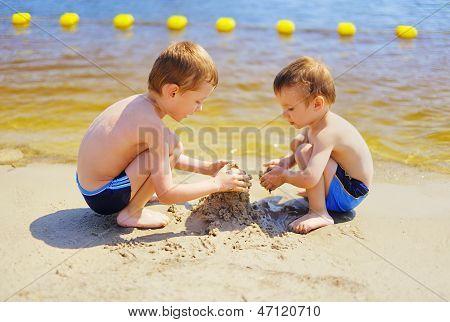 Two Boys Building Sandcastle On The Beach