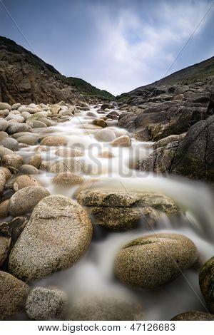 Stream feeding onto Porth Nanven beach Cornwall England