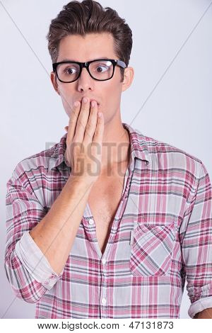 closeup portrait of a casual young man remaining speechless with his hand over his mouth and looking away from the camera. on gray background