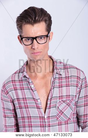 closeup picture of a casual young man looking at the camera with sadness in his eyes. on gray background