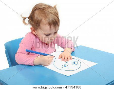 Little scholar drawing in the school desk.