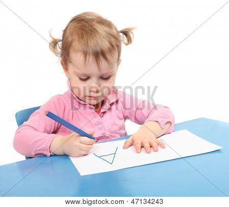 Little scholar writing in the school desk.