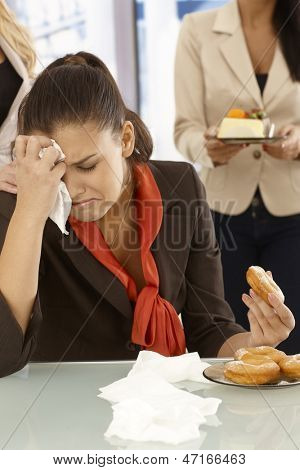Unhappy office worker sitting at desk, crying, eating doughnut.