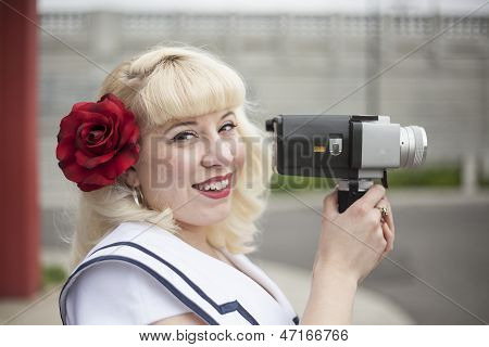 Beautiful Young Woman With Blond Hair And Movie Camera