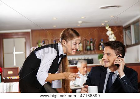 Waiter offering a pot of coffee to business man in hotel caf���©