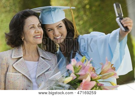 Female graduate and grandmother taking picture with cellphone outside