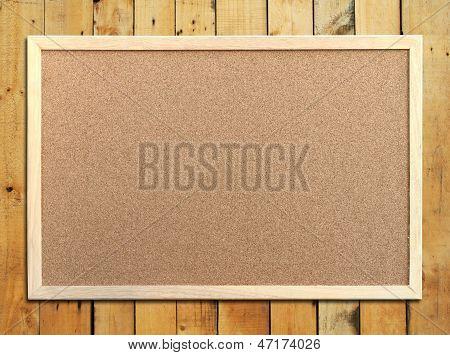 Tablero de corcho con marco de madera sobre fondo de madera