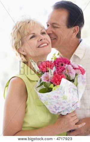 Mann und Frau holding Blumen küssen und lächelnd