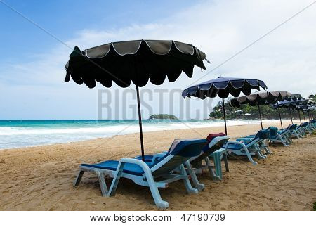 Stühle und Sonnenschirme am Strand